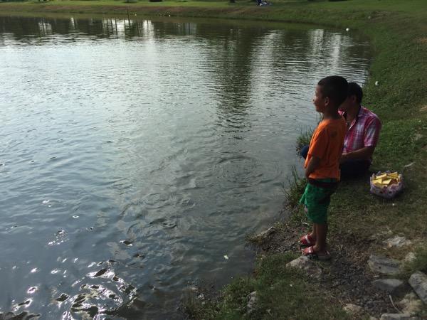 ウドンタニノーンプラジャック公園の池の魚に餌をあげる子供