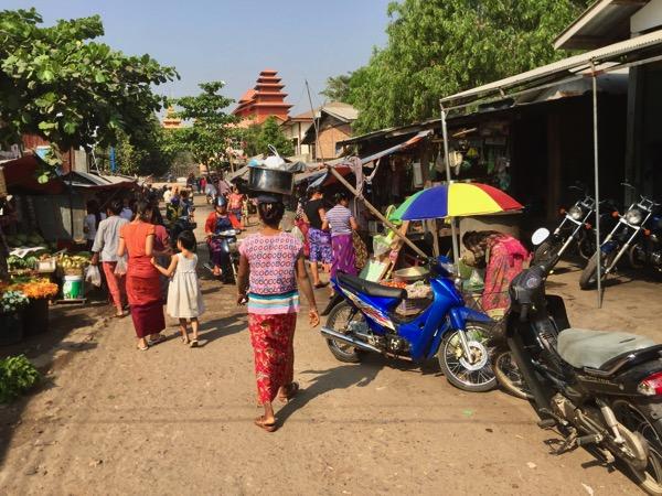 ミャワディのローカル市場で頭の上に荷物をのせてあぜ道を練り歩く現地の女性