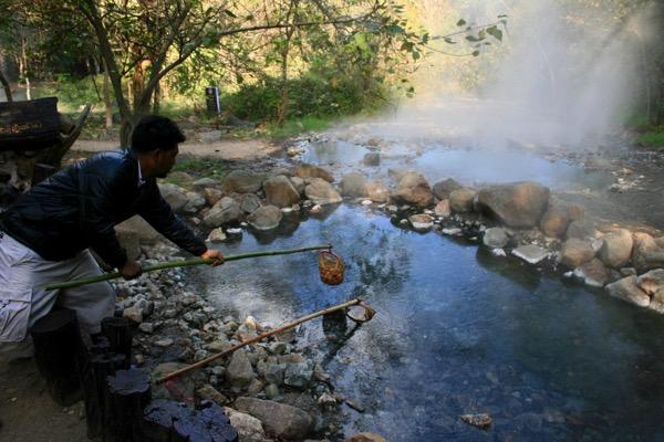 ター・パーイ温泉で竹にカゴをぶらせげて温泉玉子を作っている旅行者