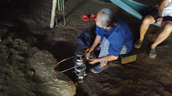 タム・ロート洞窟内でランプに火をつけるガイド